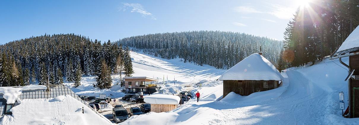 Sicht auf die Übungsloipe Nordic Arena mit Hütten und Parkplatz