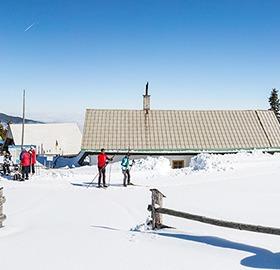 Langläuferinnen und Langläufer vor einer Hütte